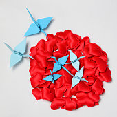 Family of paper cranes from origami in a nest of red hearts, concept love, caring for the offspring