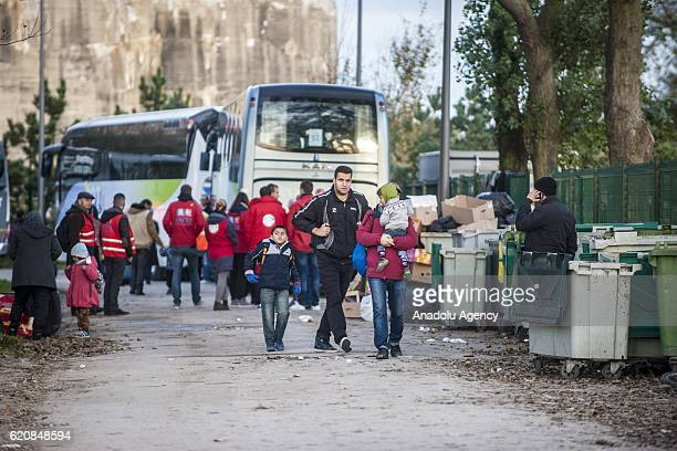 A family of refugees carry their luggages as they walk to climb into a bus after leaving the 'Jules Ferry' center reception in Calais on November 3...