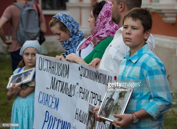 A family of Russian Orthodox Christians hold portraits of the last Russian Tsar Nikolay II and signs during a protest against the movie 'Matilda' at...