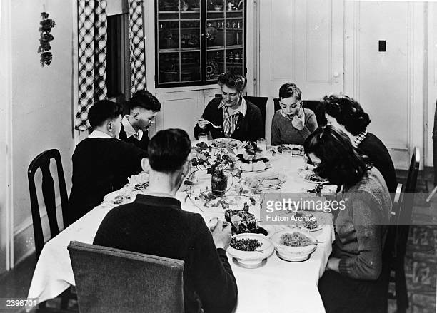 A family of seven eat a meal together at their dining room table 1940s