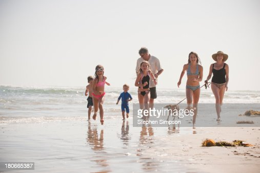 family of seven runs on the beach with their dog