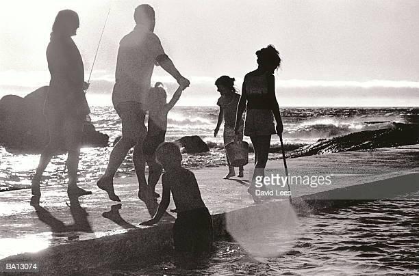 Family of six walking along jetty, rear view (B&W)