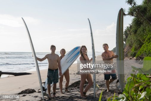 Family of surfers pose with boards on beach : Stock Photo