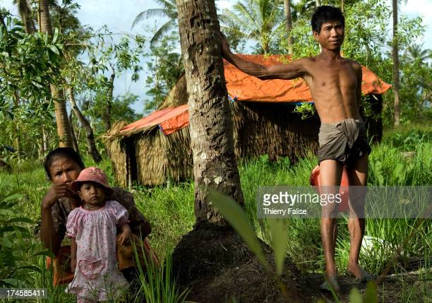 A family of survivors from cyclone Nargis stand in front of their temporary house built with palm leaves and a tarpaulin According to official...