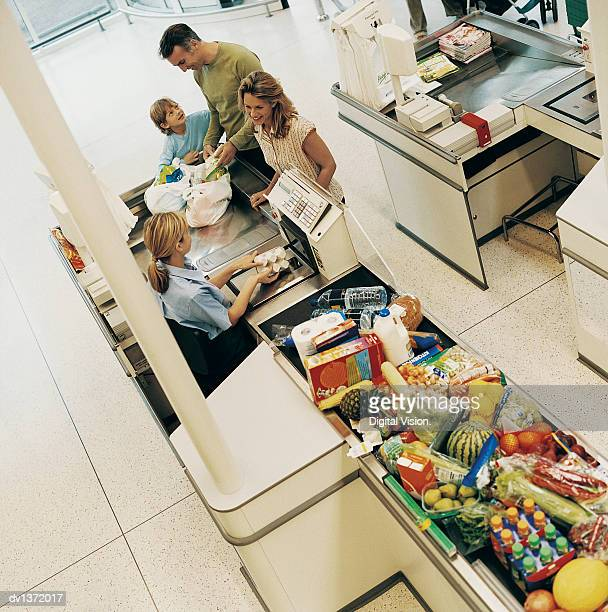 Family of Three Buying Groceries at a Supermarket Checkout