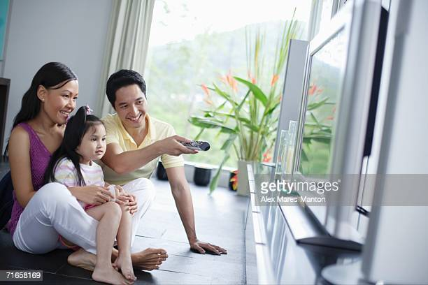 Family of three in front of TV, man pointing remote control at TV