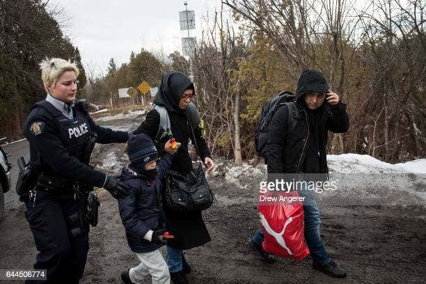 A family of three is escorted to a police vehicle by a Royal Canadian Mounted Police officer after they illegally crossed the USCanada border into...