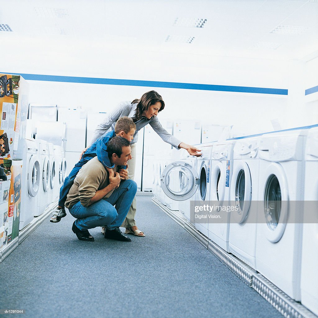 Family of Three Looking at a Washing Machine in An Aisle of a Department Store : Photo