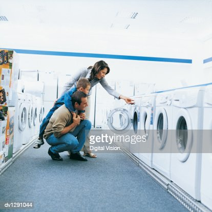 Family of Three Looking at a Washing Machine in An Aisle of a Department Store