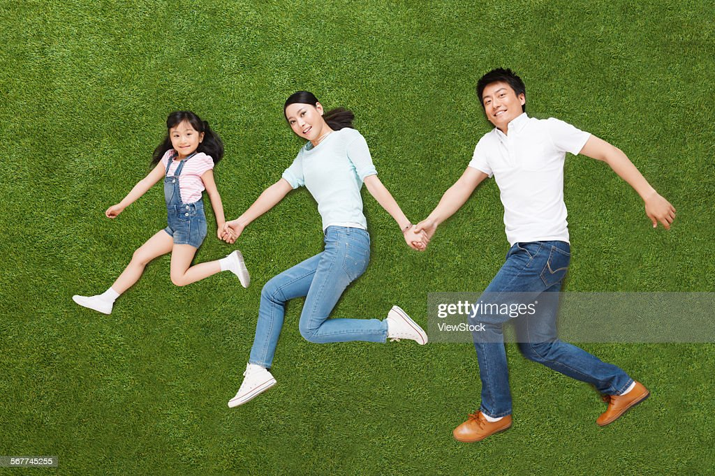 A family of three lying on the grass do running posture