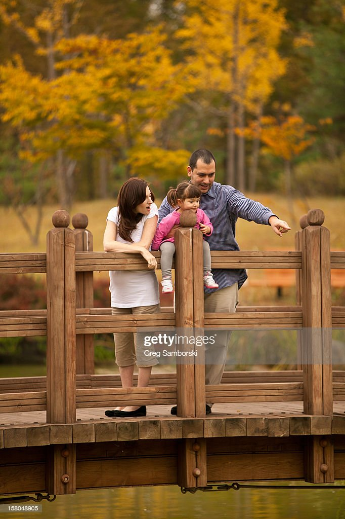 Family of three on bridge pointing : Stock Photo