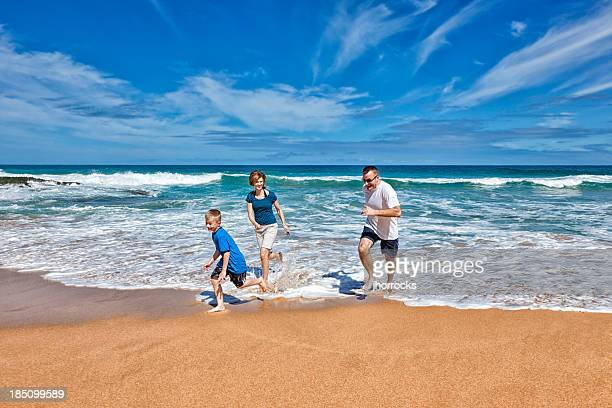 Family of Three Playing on The Beach