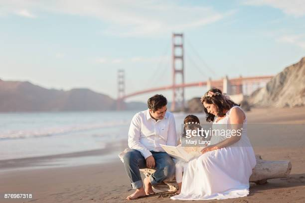 Family of three sitting at Marshall's beach with father and mother teaching their child to read a book San Francisco California USA