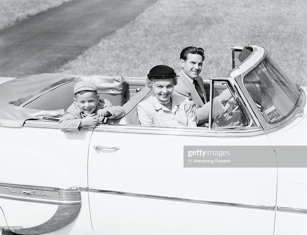 Family of three sitting in convertible car, smiling, portrait. : Stock Photo