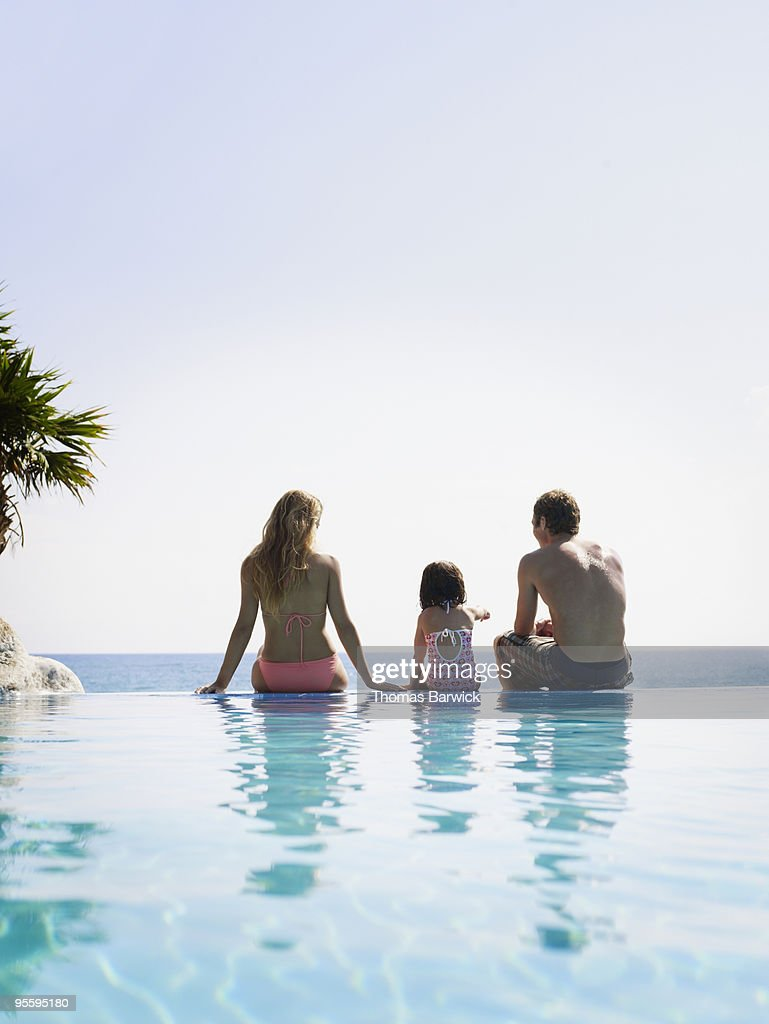 Family of three sitting on edge of infinity pool : Stock Photo