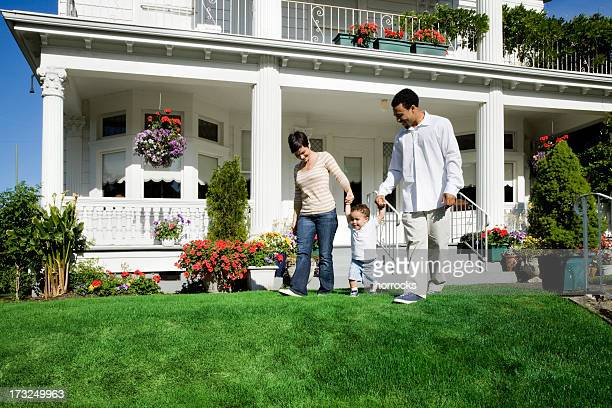 Family of Three Walking in Front Yard