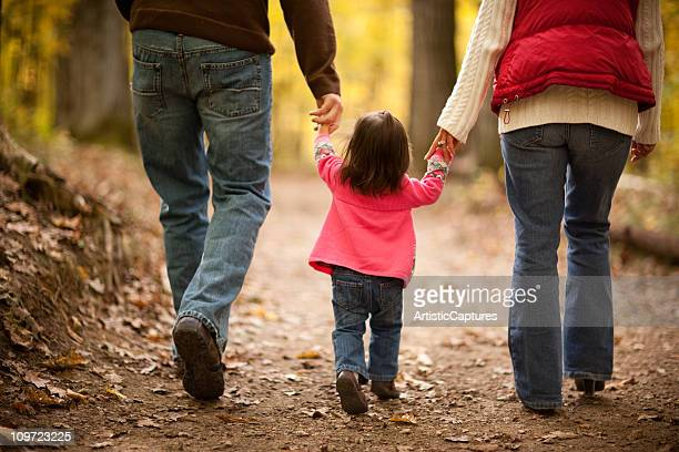 Family of Three Walking on Trail Through Autumn Woods