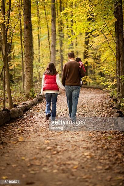 Famiglia di tre piedi sul sentiero attraverso boschi autunnali