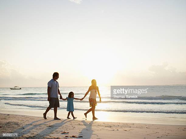 Family of three walking on tropical beach