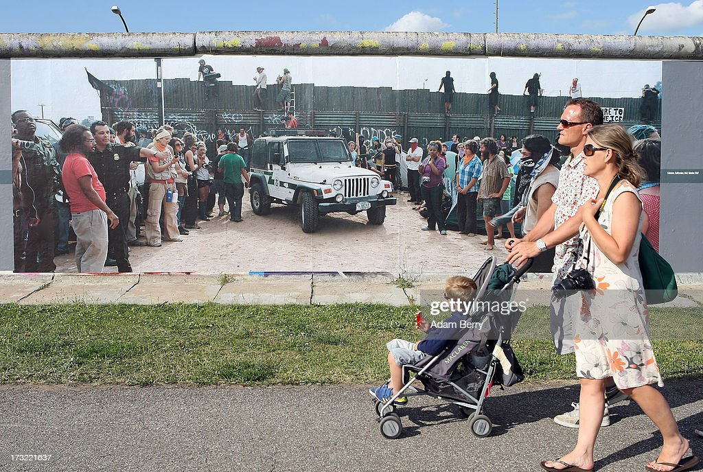A family of tourists passes a photo of the United States-Mexico border in Calexico, California, hanging as part of the 'Wall on Wall' exhibition at the East Side Gallery section of the former Berlin Wall on July 10, 2013 in Berlin, Germany. A series of photos shot since 2006 by photographer Kai Wiedenhoefer hanging on the Western, river Spree side of the Wall features large pictures of separation barriers in Baghdad, Korea, Cyprus, Mexico, Morocco, Israel, Belfast, and in the former East Germany itself. The opposite side of the stretch of the original Wall is known as East Side Gallery, a memorial to peace and freedom covered in murals questioning the legacy of the original Wall, and the subject of several demonstrations earlier in March this year when a section of it were threatened with removal to make way for a construction site for luxury apartment buildings, discussion of which is still ongoing with a decision expected to be reached in early August.