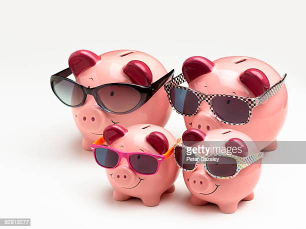 Family of vacation piggy banks in sun glasses.