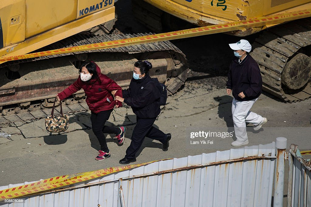 Family of victim run near a collapsed building on February 7, 2016 in Tainan, Taiwan. A magnitude 6.4 earthquake hit southern Taiwan early Saturday, toppling several buildings, killing at least fourteen people, and leaving over one hundred missing in Tainan.