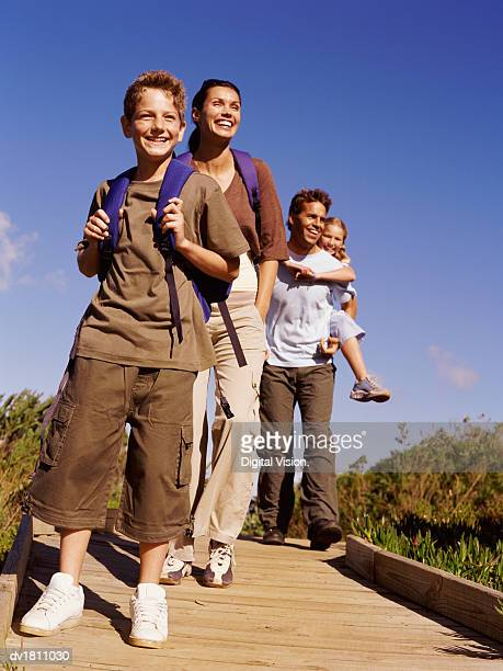 Family on a Day Out Walking Along a Wooden Walkway