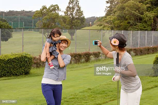 Family on a golf course. A woman using a camera.