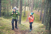 family on a hike in the forest with baby in child carrier on father's back