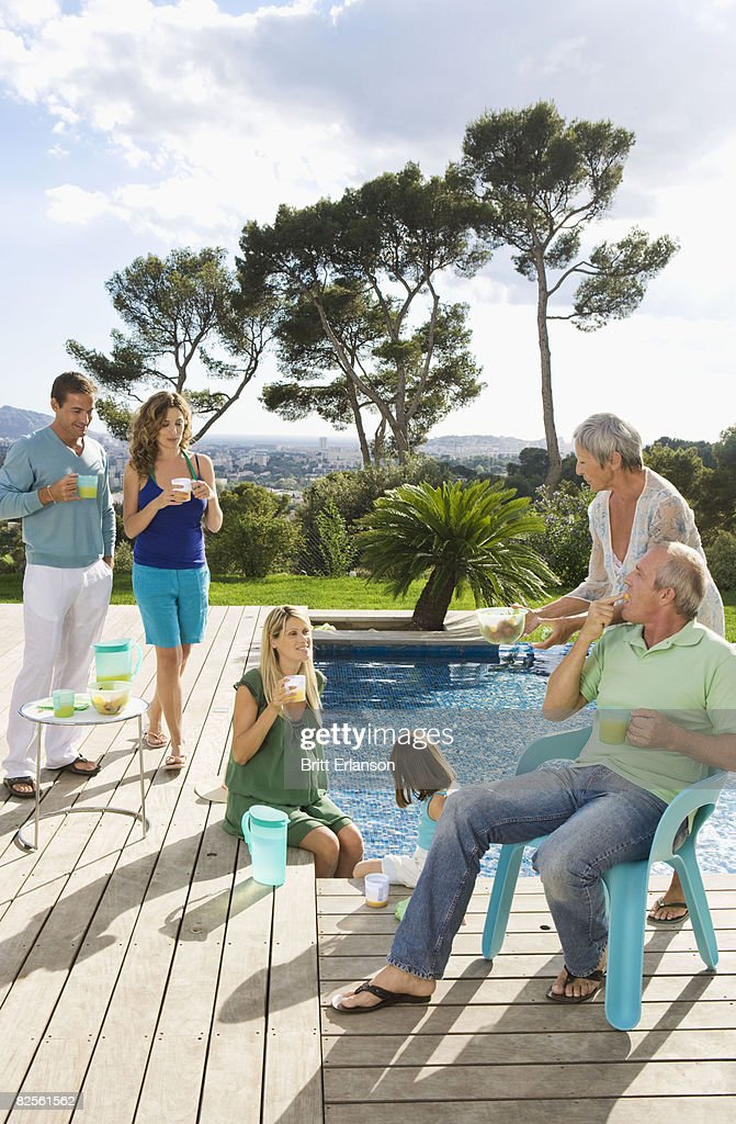 Family on a wooden terrace by a pool stock photo getty for Kids on the terrace