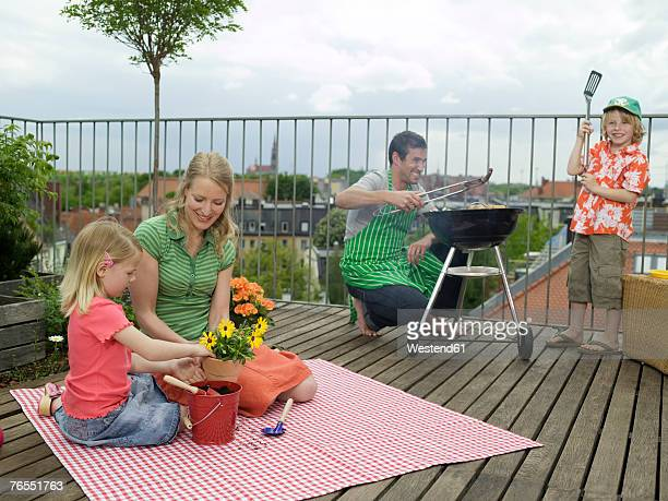 Parents with children (6-9) on balcony, man preparing food on barbecue
