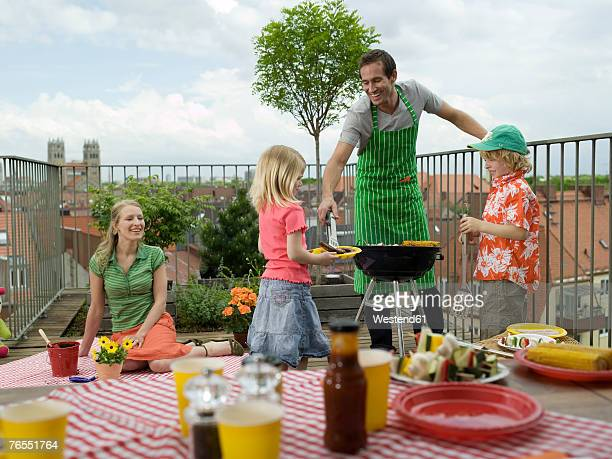 Parents with children (6-9) on balcony, father serving daughter