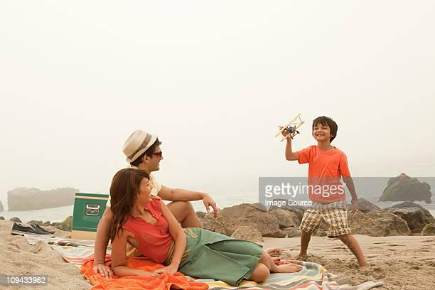 Familie am Strand, Junge spielt mit Spielzeug Flugzeug