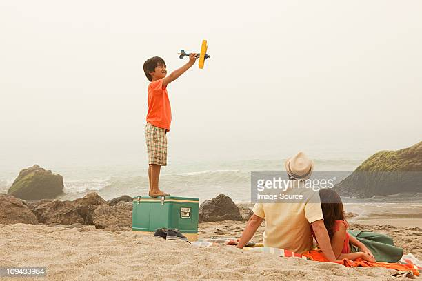 Family on beach, boy playing with toy plane