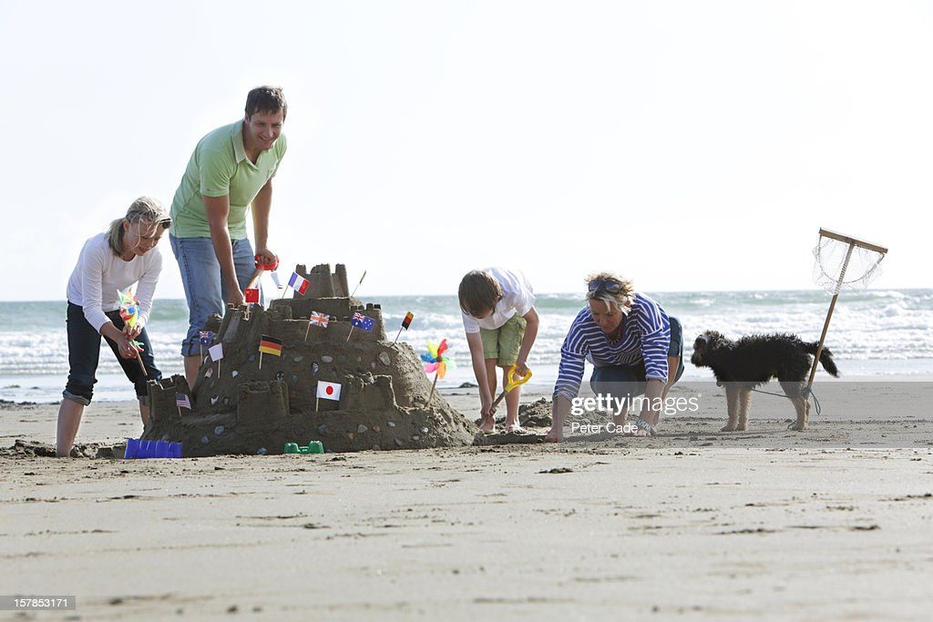 Family on beach building large sandcastle : Stock Photo