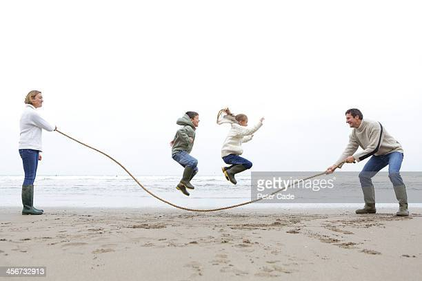 Family on beach, children jumping over rope