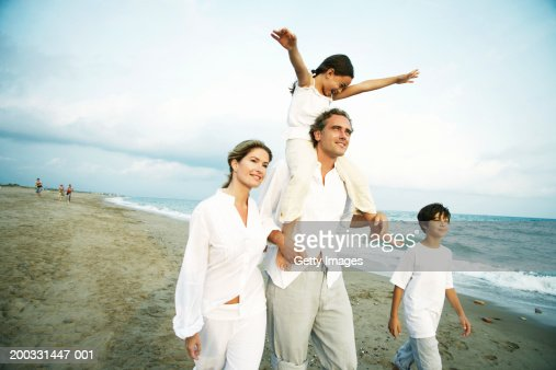 Family on beach, girl (6-8) on father's shoulders, arms outstretched : Foto de stock