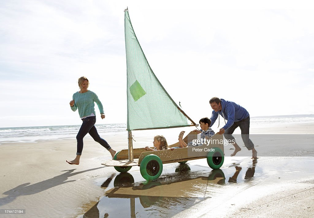 Family on beach in go kart with sail