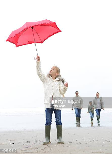 Family on beach in winter, girl with red umbrella