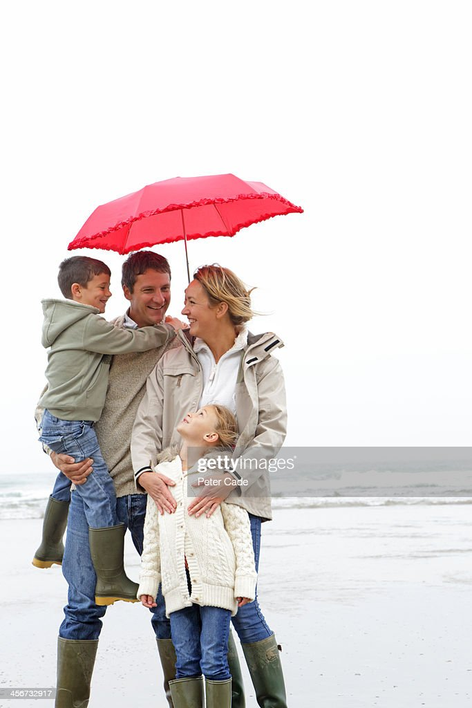 Family on beach in winter under red umbrella