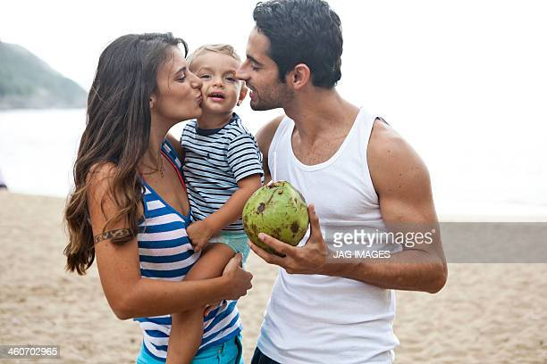 Family on beach, mother kissing son on cheek