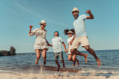 happy african american family holding hands and jumping on beach