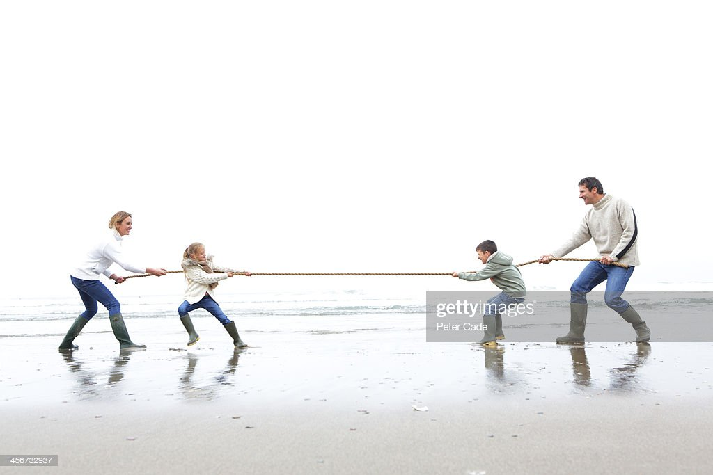Family on beach playing tug of war : Stock Photo