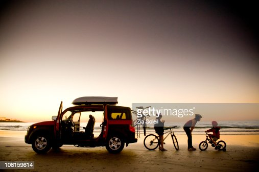 family on beach with bikes and car, sunset : Stock Photo