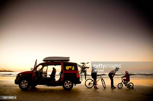 family on beach with bikes and car, sunset