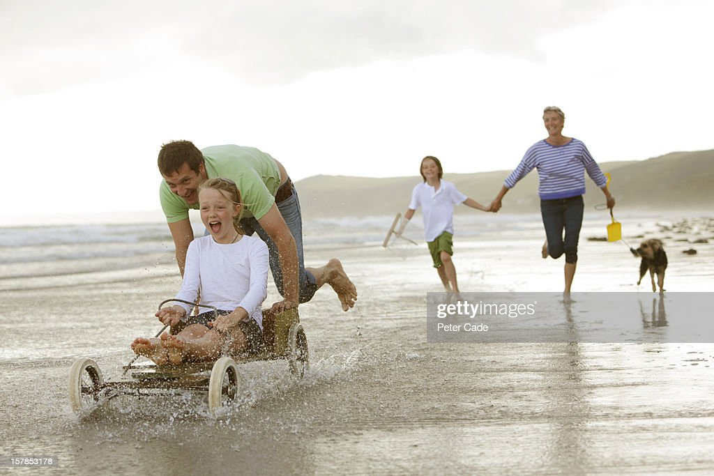 Family on beach with home made go-kart : Stock Photo