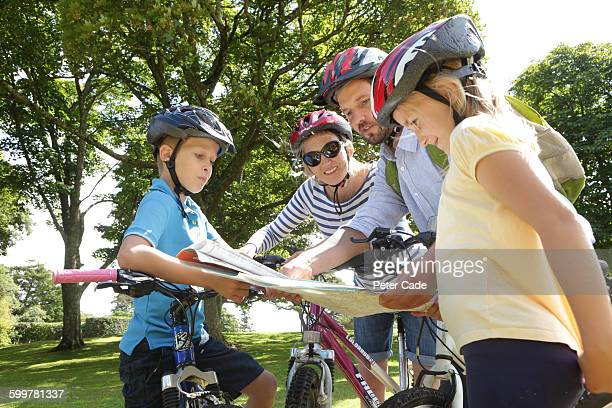 Family on bikes looking at map