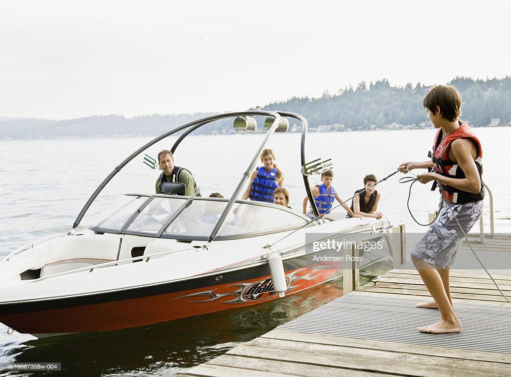 Family on boat, teenage boy holding rope : Stock Photo