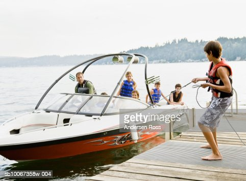 Family on boat, teenage boy holding rope : Stock Photo