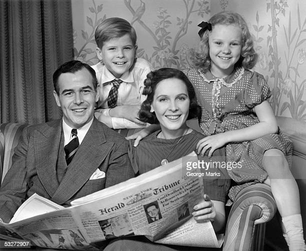 Family on couch w newspaper